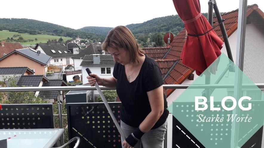 Nicole auf dem Balkon, sie putzt