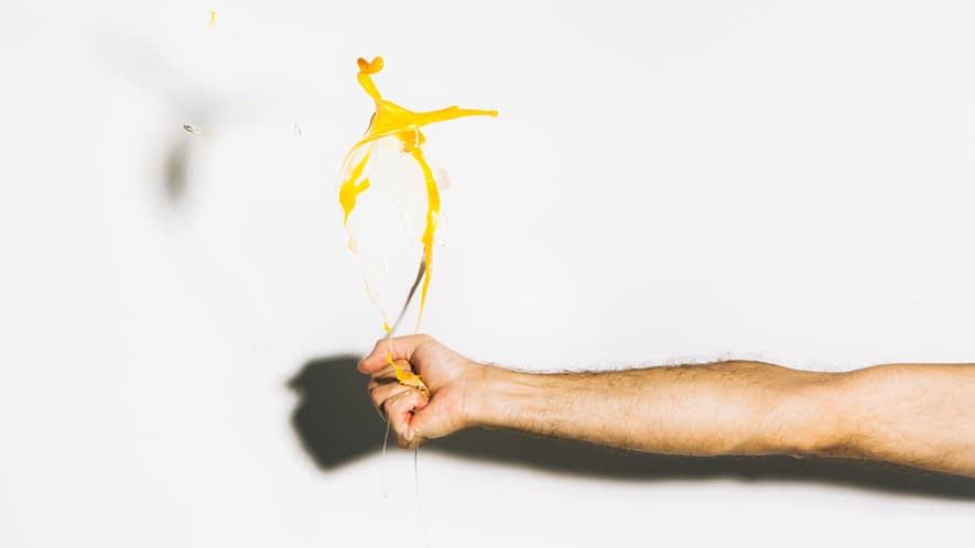 Hand, die ein Ei zerdrückt