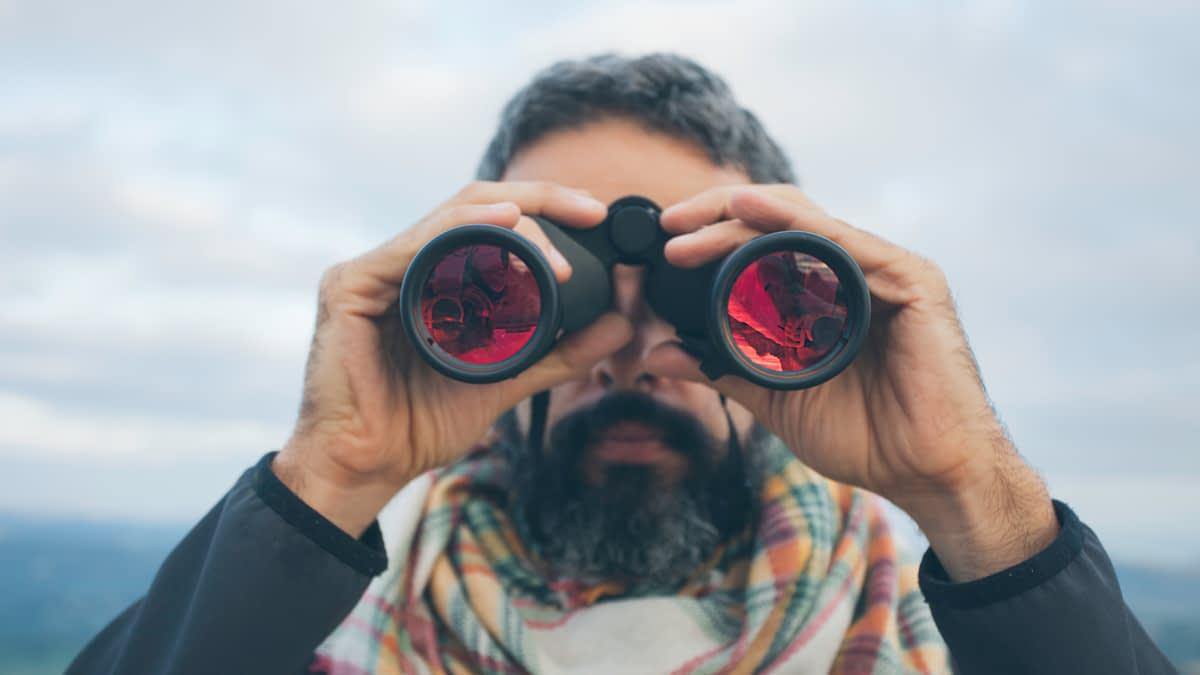 Mann schaut durch ein Fernglas