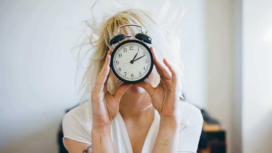 Frau hält einen Wecker vor ihr Gesicht
