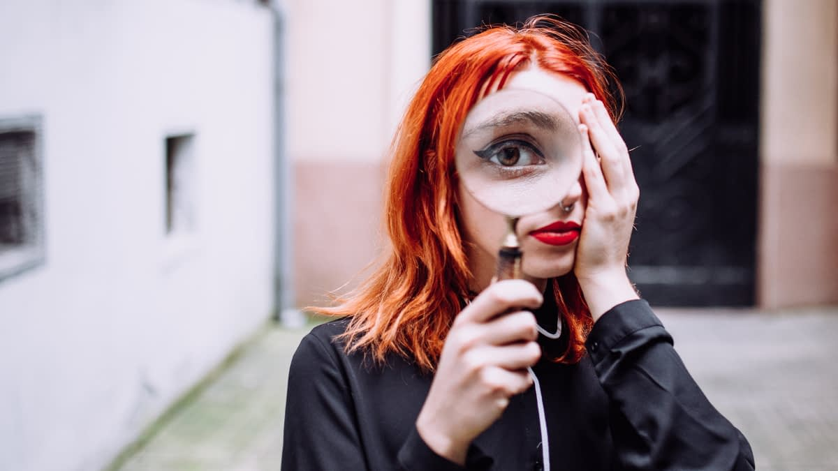 Frau schaut durch Lupe