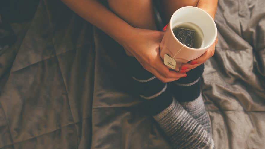 Ausschnitt von Frau mit Teetasse in der Hand
