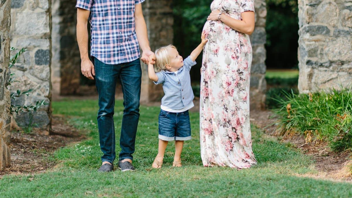 Kleines Kind an den Händen seiner Eltern