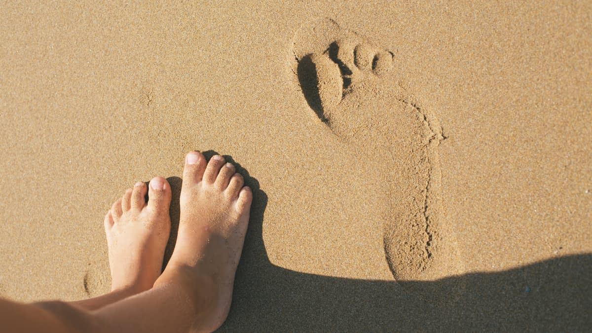 Füße im Sand neben Fußabdruck