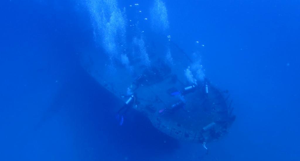 divers near a wreck in oahu