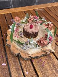 Blumenkranz auf Holzbrett mit Minitörtchen
