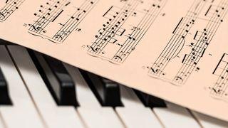 nuottilehti pianon koskettimien päällä