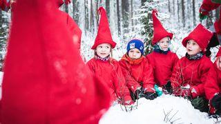 Lapset istuvat piirissä ulkona tonttupuvut ja -lakit päässä.