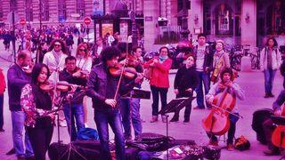 Jousisoitinyhtye soittamassa ulkotiloissa, yleisö seuraa.