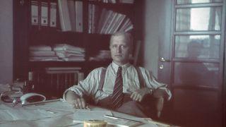 Jalmari Lankinen istuu toimistossaan, kravatti kaulassaan ja kynä kädessä. Taustalla näkyy kirjahyvvy, missä mappeja ja papereita.