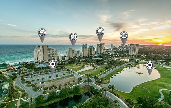 Luftaufnahme einer Parkanlage und Stadt am Meer bei Sonnenuntergang