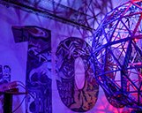 Innenaufnahme eines Teils der Ausstellung der STROKE Art Fair im Schwarzlicht