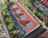 Luftaufnahme eines großen Mehrfamilienhauses mit rotem Dach