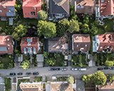 Drohnenaufnahme einer Straße in einer Wohnsiedlung aus der Vogelperspektive
