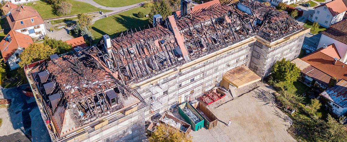 Luftaufnahme von einem großen Haus aus der Entfernung mit abgebranntem Dach