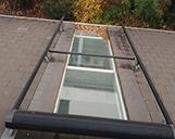 Drohnenaufnahme eines Dachfensters mit durch Laub verstopfter Dachrinne