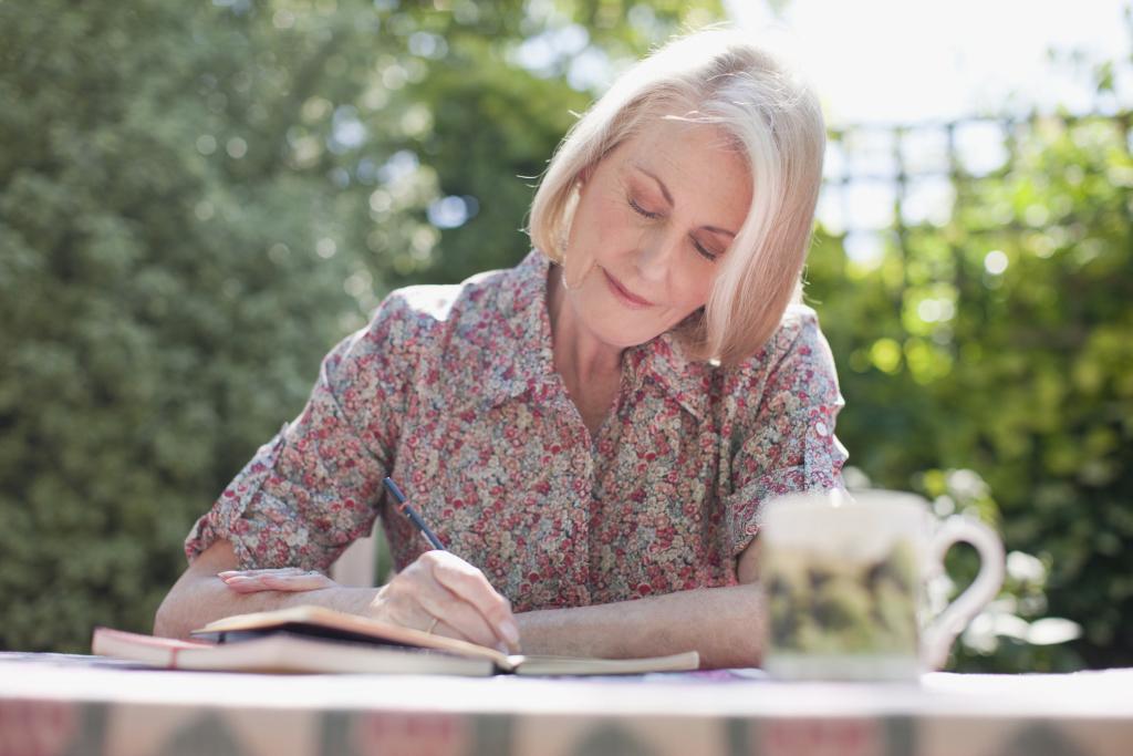 Freu im Garten schreibt in einem Notizbuch
