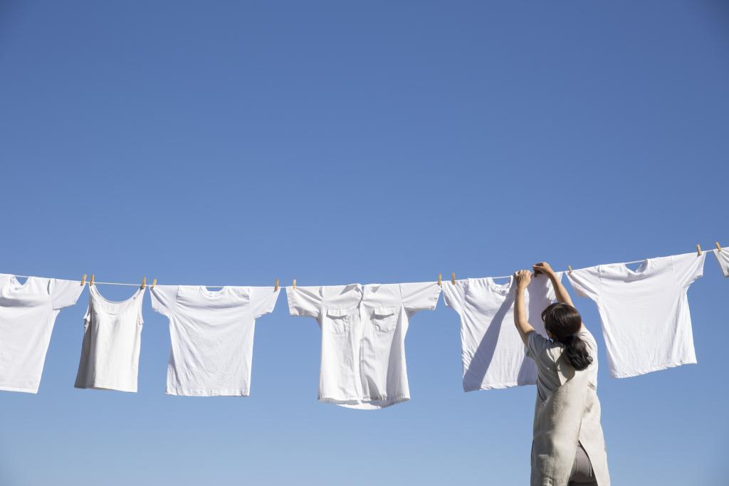 Frau hängt weiße Kleidung auf Wäscheleine