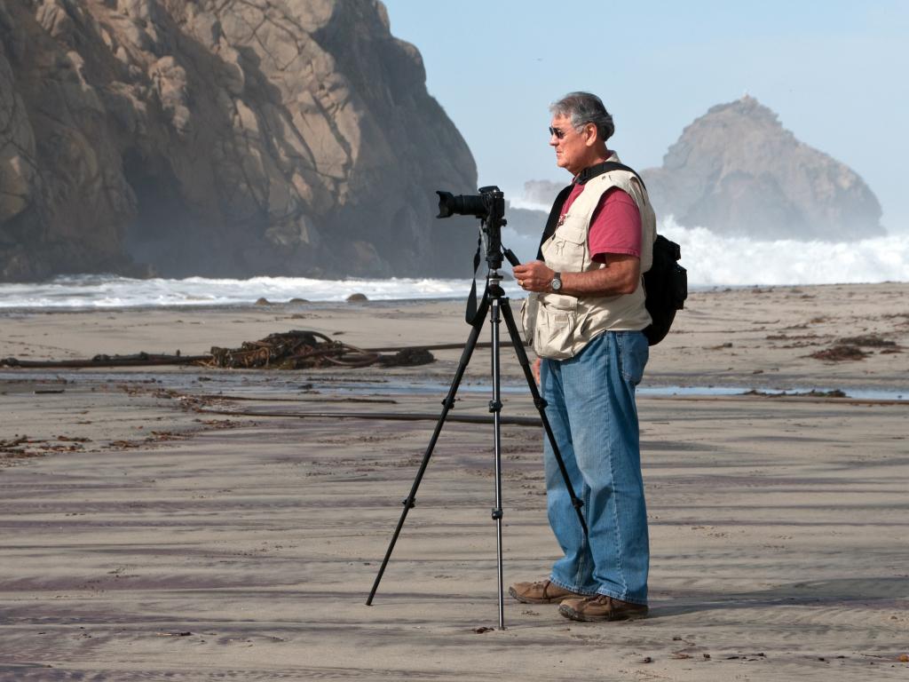 Fotograf mit Stativ an Meeresküste
