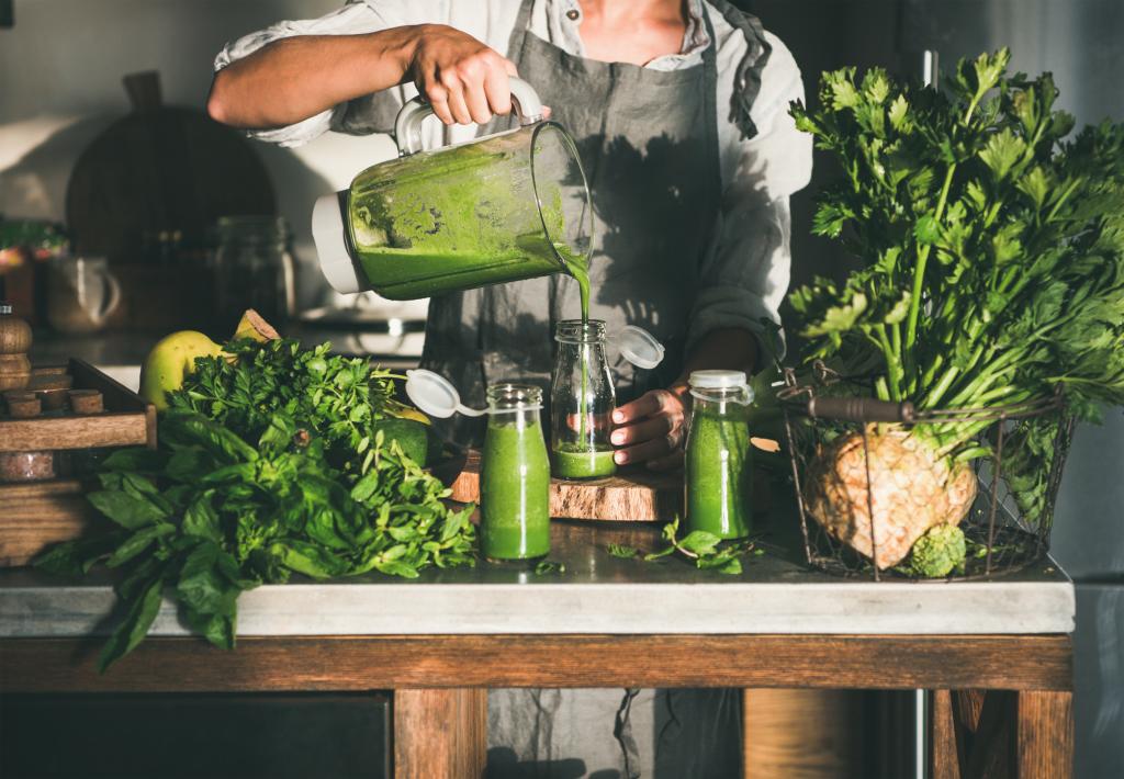 Frau beim Zubereiten grüner Smoothies