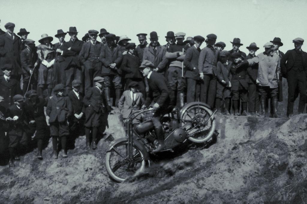 Zuschauer gruppieren sich um einen Motorradfahrer, ca. 1930er
