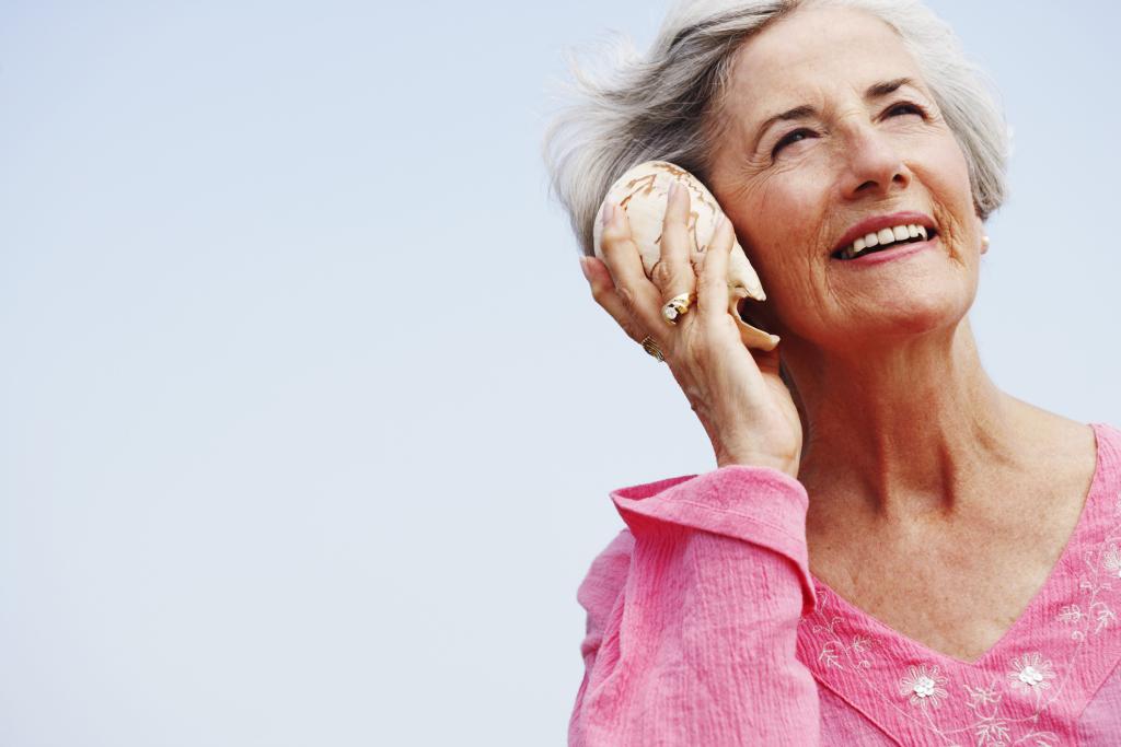 Frau hält Muschel ans Ohr