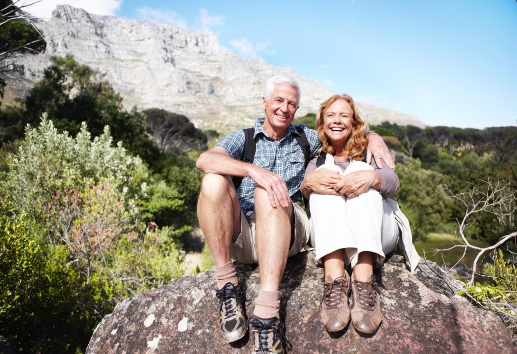 fröhliches Paar sitzt auf einem Stein in den Bergen