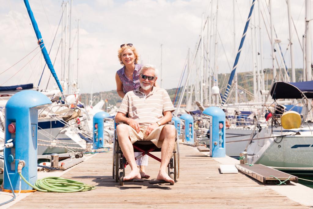 Frau schiebt Mann im Rollstuhl auf einem Bootssteg