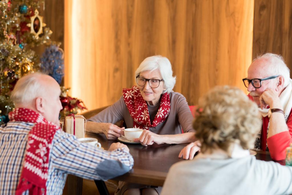 Senioren am Tisch vor einem Weihnachtsbaum