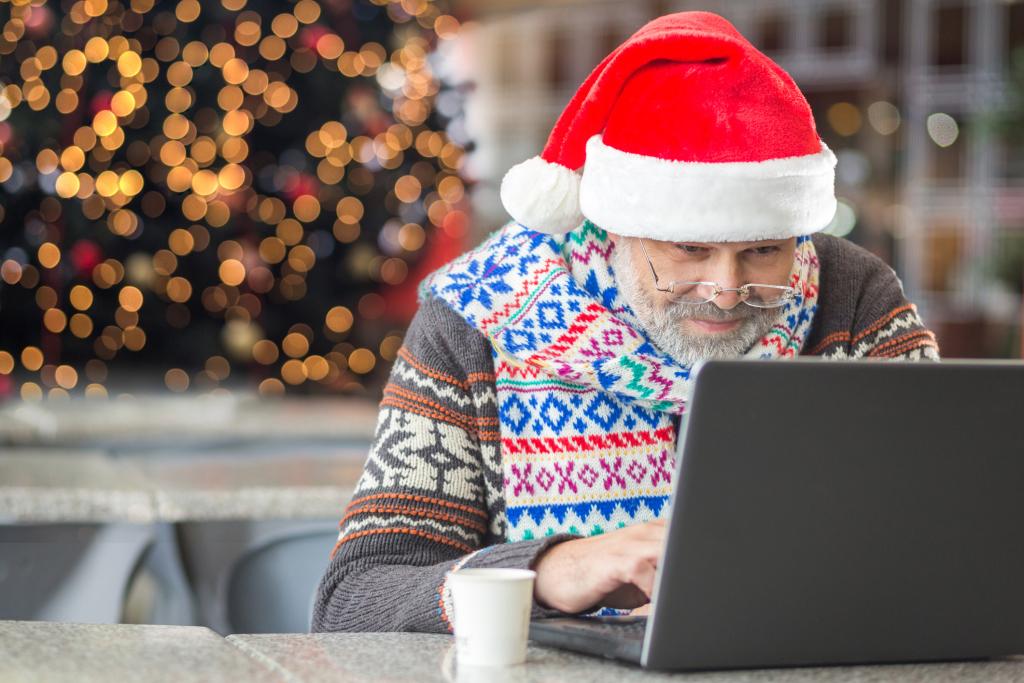 Weihnachtlich gekleideter Senior vor dem PC