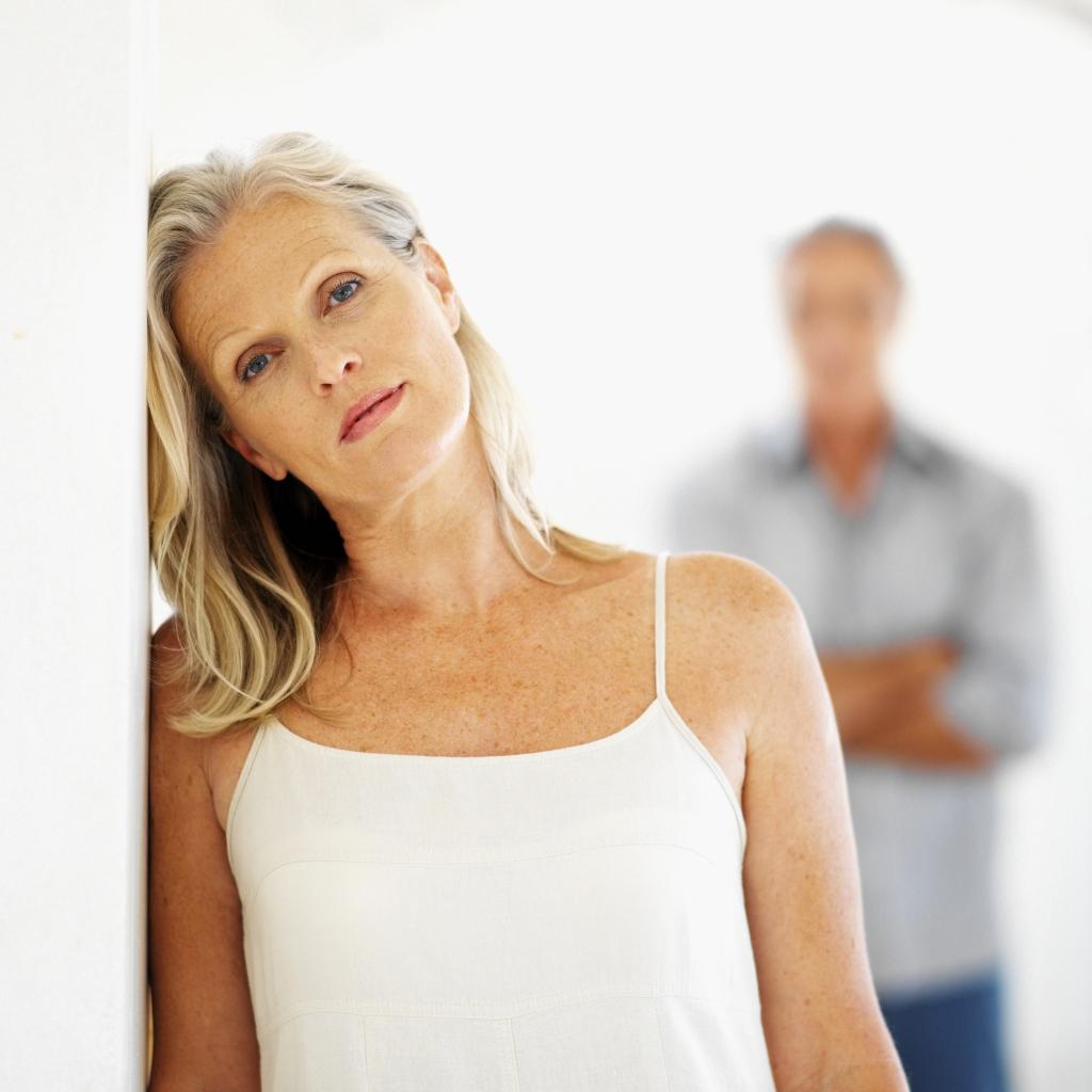 Frau an der Wand lehnend, Mann verschwommen im Hintergrung