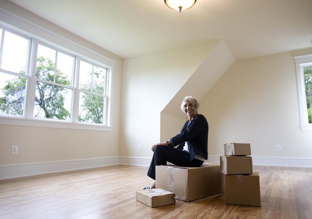 Frau sitzt in leerem Raum auf Umzugkartons