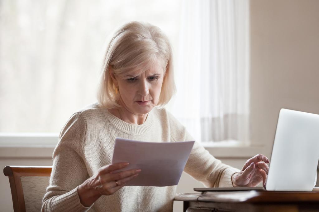 Frau vor dem Laptop liest einen Brief