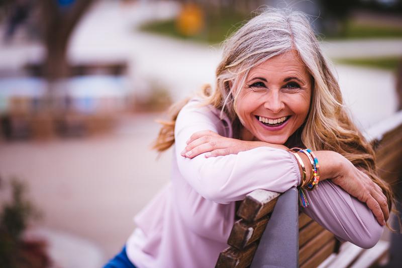 Frau lacht auf einer Parkbank