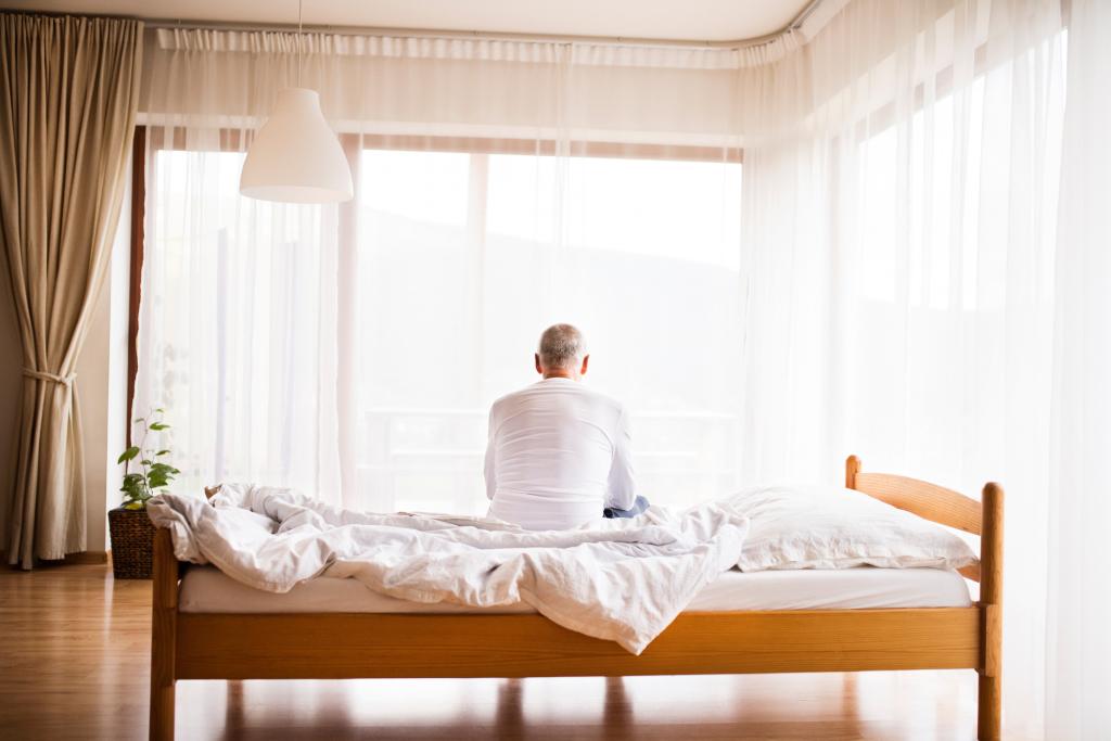 Mann sitzend auf dem Bett