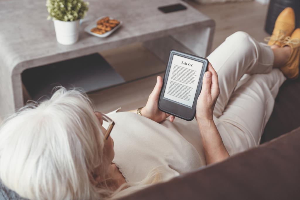 Frau auf dem Sofa liest ein E-Book