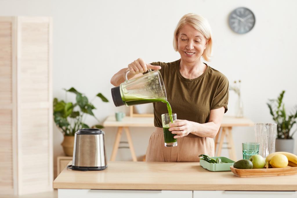 Frau gießt grünen Smoothie in ein Glas
