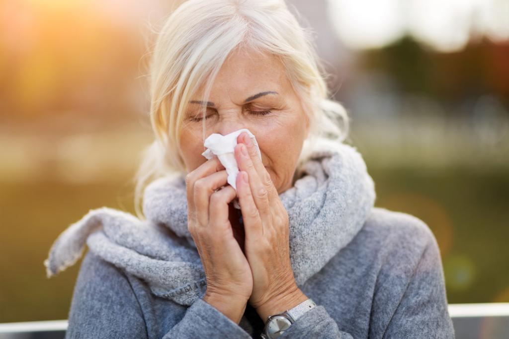 Ältere Frau putzt sich die Nase