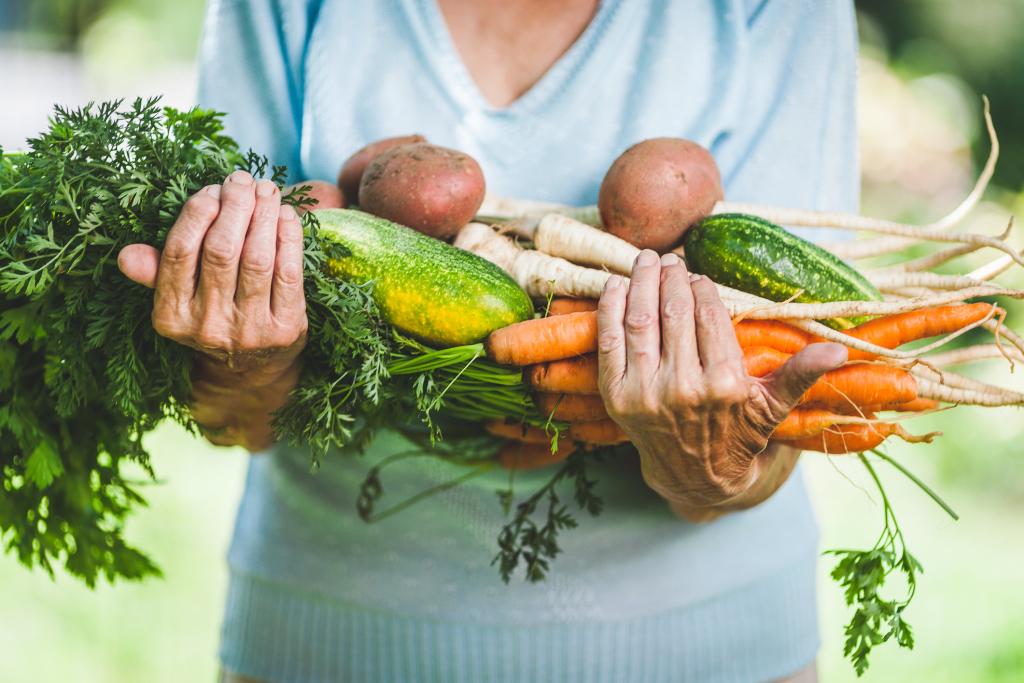 Frau hält gesunde Lebensmittel in den Armen