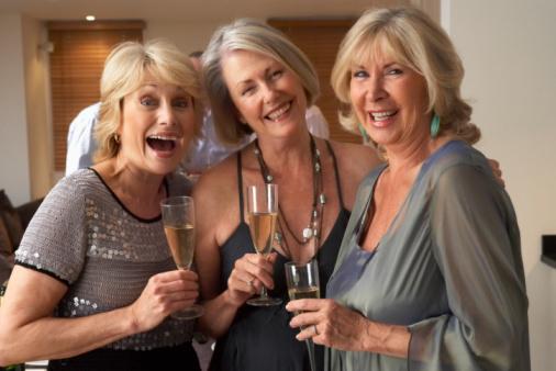 Drei Damen mit Sektgläsern anstoßend