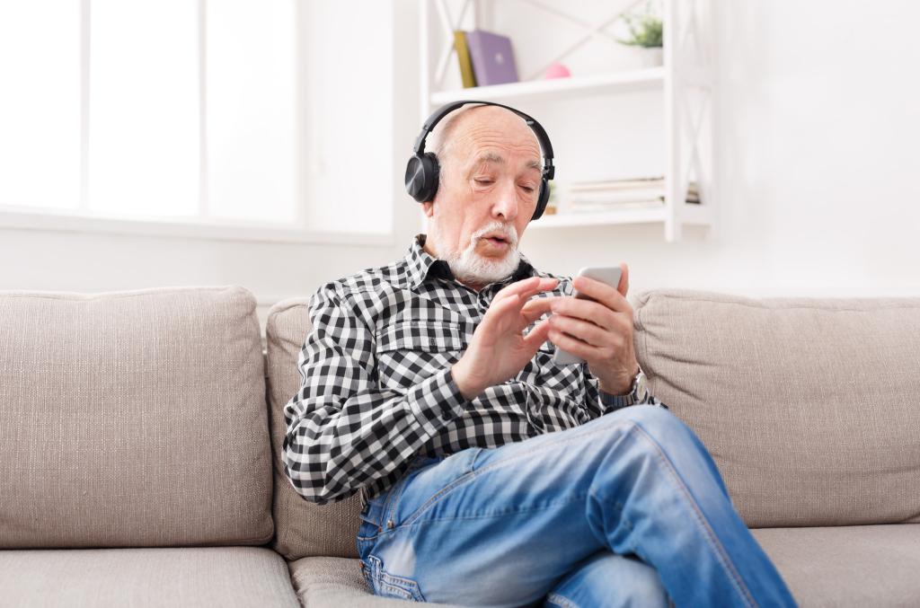 Mann mit Kopfhörern und Handy auf dem Sofa