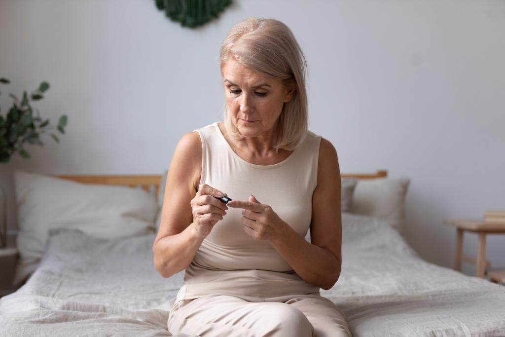 Diabetikerin bei Blutabkontrolle auf ihrem Bett