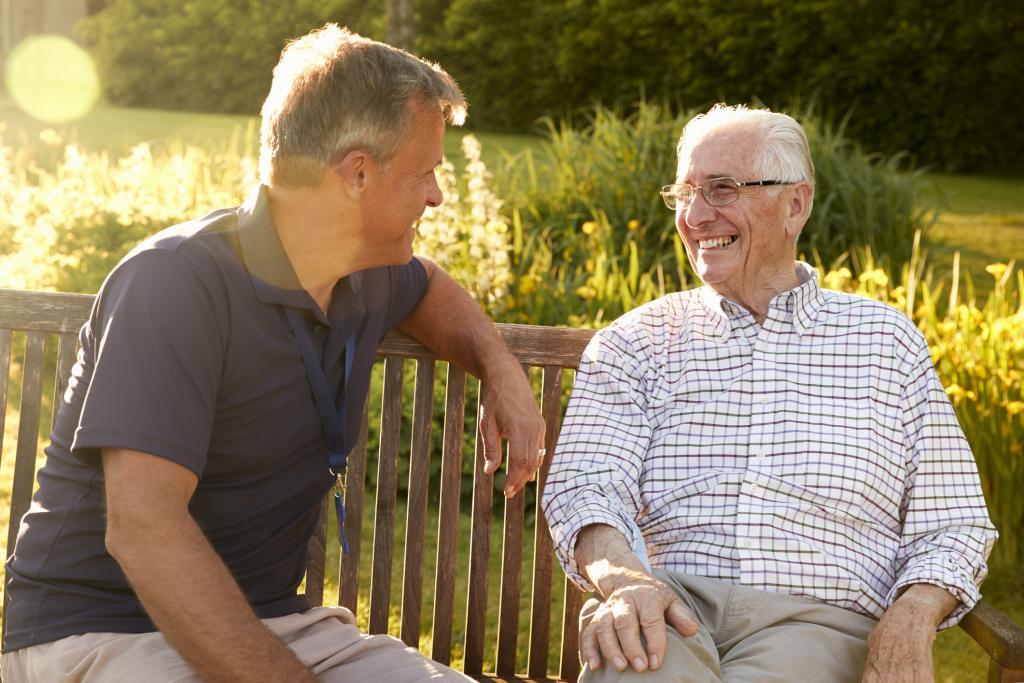 zwei Männer auf einer Gartenbank im Gespräch