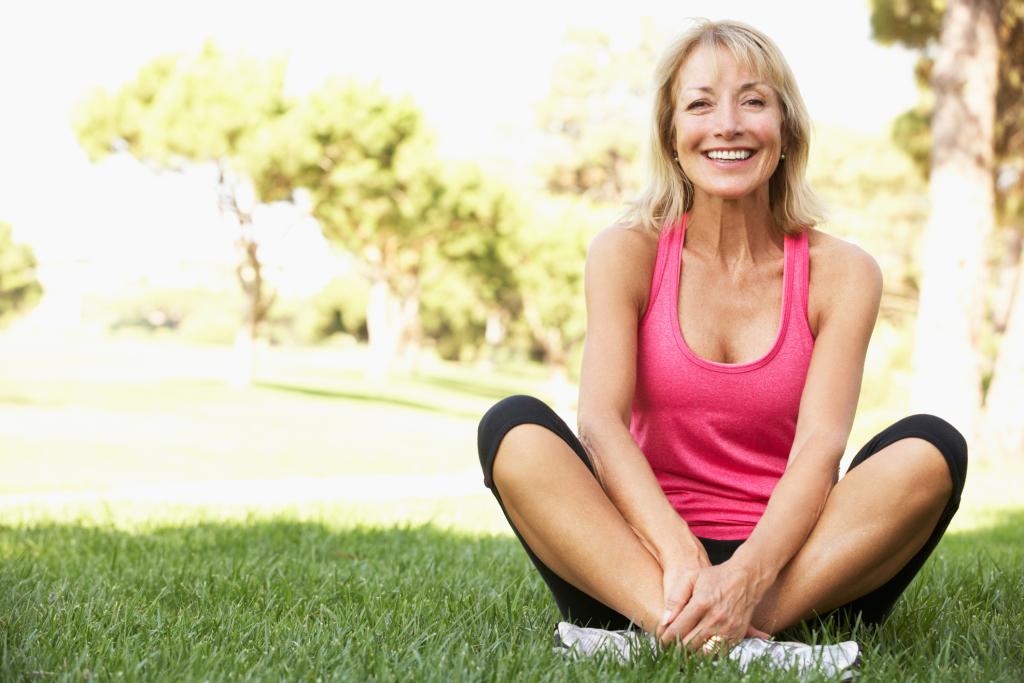 lächelnde Frau sitzt im Schneidersitz auf dem Rasen