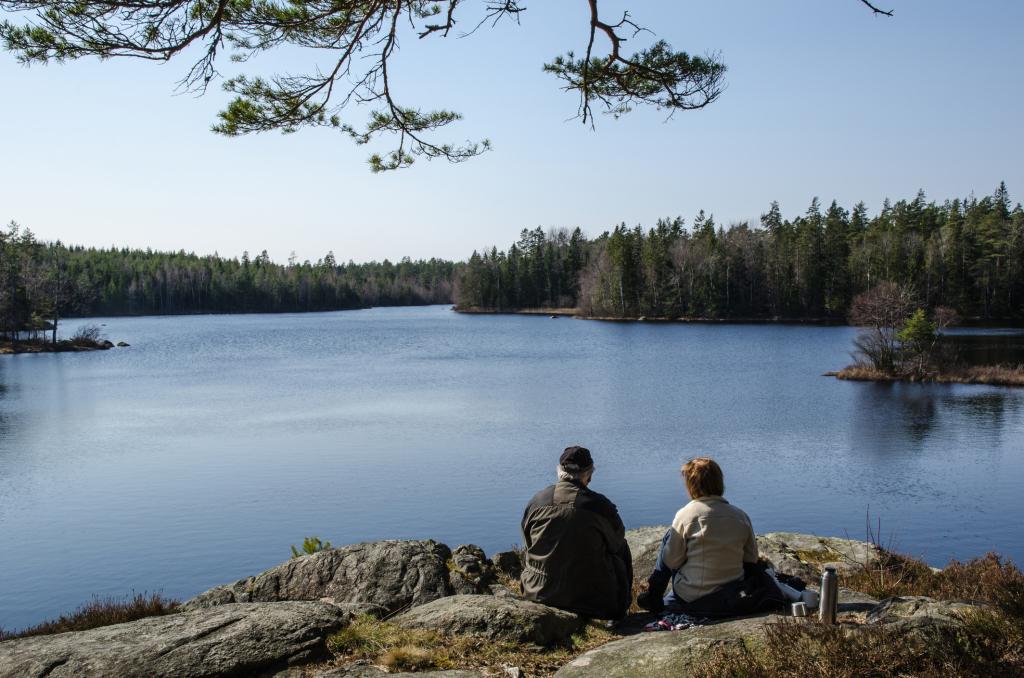 Paar sitzend an einem See mit Bergen drumrum