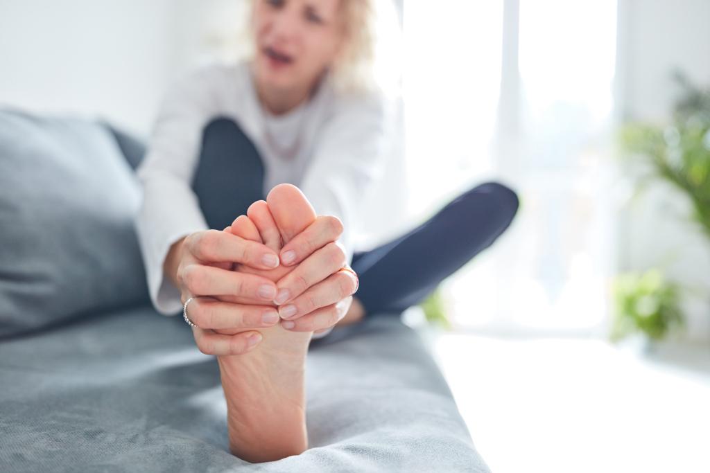 Frau mit Schmerzen im Fuß