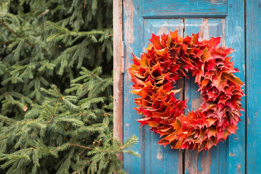 Herbstkranz aus roten Ahornblättern auf Holztür