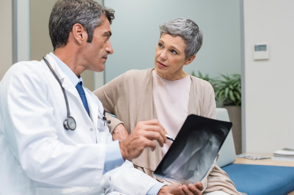 Arzt erklärt einer Patientin ein Röntgenbild