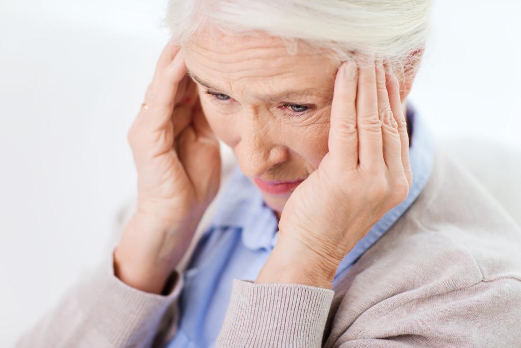 Frau hält sich den schmerzenden Kopf