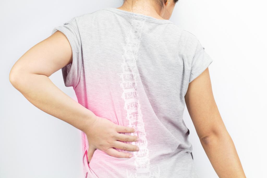 Frau hält sich den schmerzenden Rücken